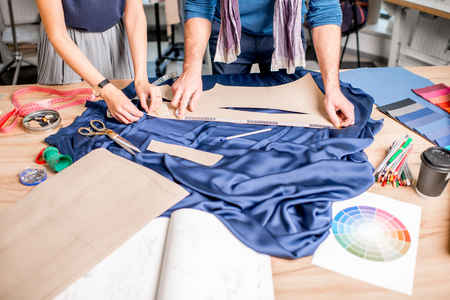 Cutting blue fabric on the table full of tailoring tools. Close-up view on the hands and fabric with no face Foto de archivo