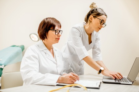 Senior doctor and young woman assistant working together with laptop and documents in the gynecological office