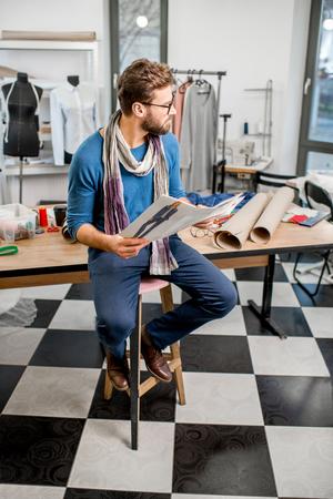 仕立て道具や服でいっぱいのスタジオで服のスケッチで座っているハンサムなファッションデザイナーの肖像画