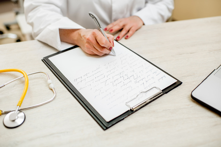 Senior doctor writing recipe on the table with documents. Close-up view with no face