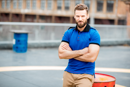 Lifestyle portrait of a handsome man in blue t-shirt sitting on a barrel outdoors on the helicopter platform Foto de archivo