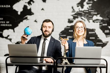 Paar van reismanagers die online met laptops en hoofdtelefoons op het bureaukantoor werken met wereldkaart op de achtergrond