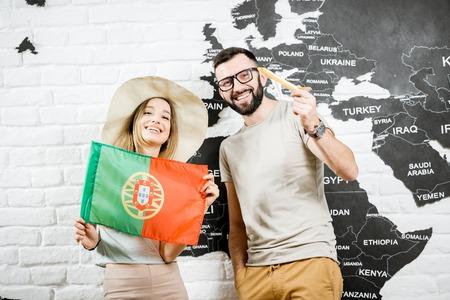 Paar van jonge reizigers die zich met Portugese vlag dichtbij de muur met wereldkaart bevinden, die over de zomervakanties dromen in Portugal