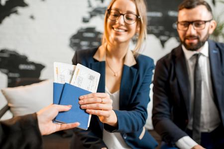 Jong businesscouple die een reis met agentenzitting kiezen op het reisbureaukantoor met wereldkaart op de achtergrond
