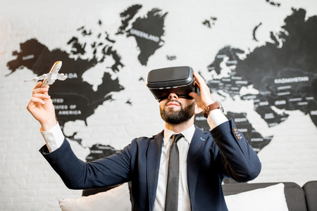 c3f54c6f7444 Businessman using virtual reality glasses sitting indoors with world map on  the background Stock Photo