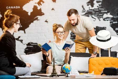 Junge reizende Paare, die mit Manager im Reisebüro vorbereitet für Sommerferien sitzen Standard-Bild - 92670479