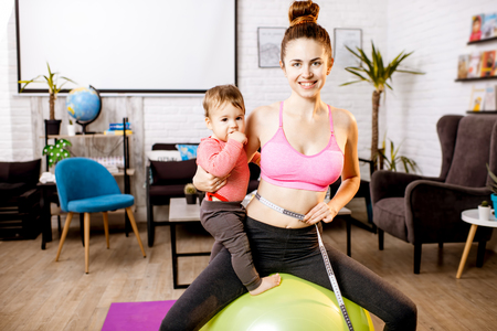 Young mother in sportswear measuring her waist worried about her weight after the child birth sitting with her baby son during the exercise
