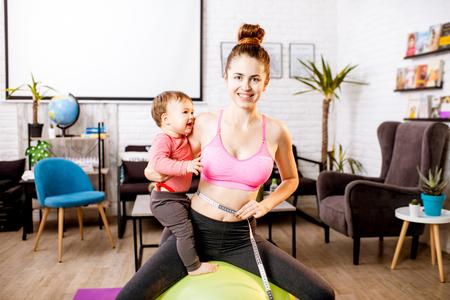 Jeune mère en vêtement de sport mesurant sa taille inquiète pour son poids après la naissance de l'enfant assise avec son bébé pendant l'exercice Banque d'images - 93394056
