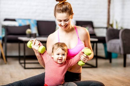 Portrait of a happy mother with her baby son exercising with dumbbells at home Foto de archivo