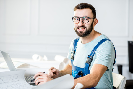 Handsome repairman or foreman in uniform working with laptop and architectural drawings at the office Stock fotó - 93877212