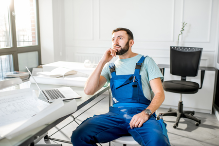 Portrait of a handsome repairman in workwear relaxing after the work in the office with laptop and paper drawings Stock Photo