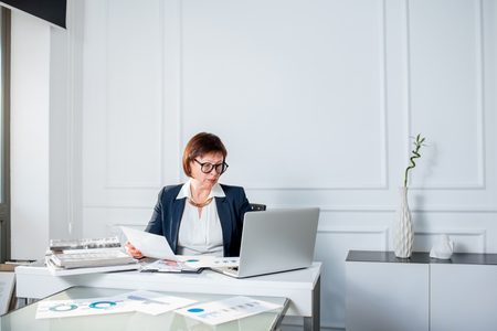 Elegant senior businesswoman dressed in the suit working with laptop and documents at the white office. Wide angle view with copy space