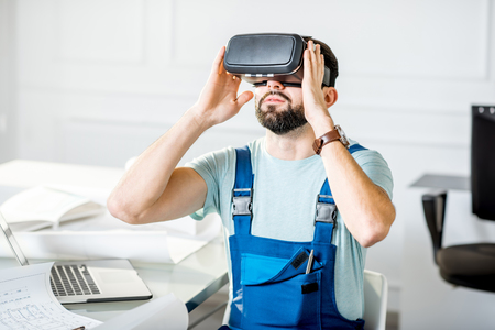 Handsome foreman in working uniform using vr glasses to imagine projected environment sitting at the office