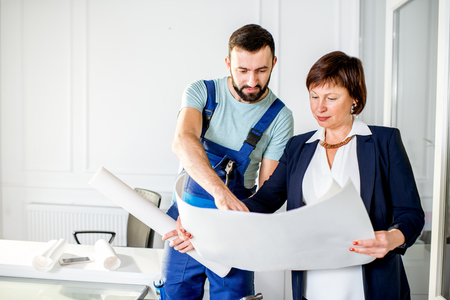 Repairman discussing the project with senior woman architect or client at the office Stock Photo