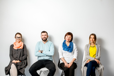 Portrait of a people dressed casually in colorful clothes sitting indoors on the white wall background