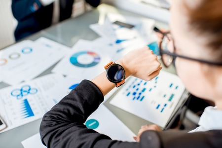 Businesswoman looking on the smart watch with documents on the background Stock Photo
