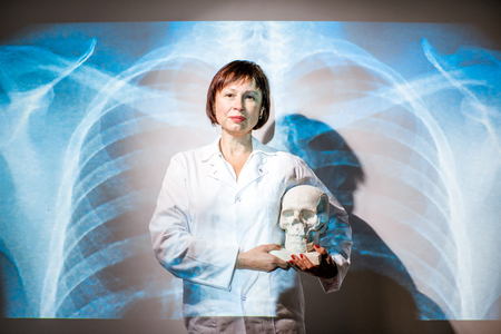 Portrait of a senior woman doctor in uniform with projected x-ray of human lungs Banco de Imagens