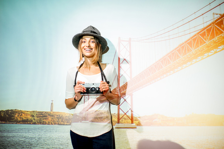 Portrait of a young woman traveler with projected image of landscape view on the famous bridge in Lisbon city