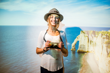Portrait of a young woman traveler with projected image of the famous rocks in Etretat in France