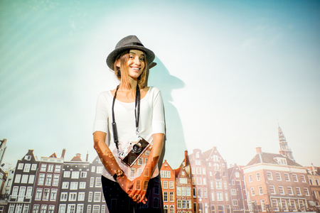 Portrait of a young woman traveler with projected image of beautiful buildings in Amsterdam city