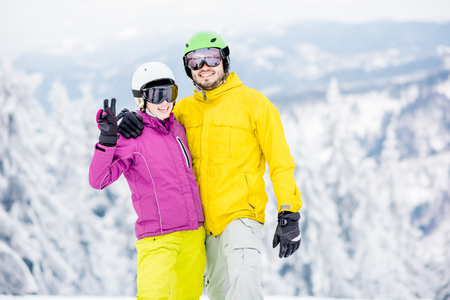 Portrait of a young and happy couple snowboarders in colorful sports clothes standing together on the snowy mountains