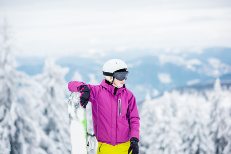 Portrait of a young woman snowboarder standing outdoors on the snowy mountains Stock Photo