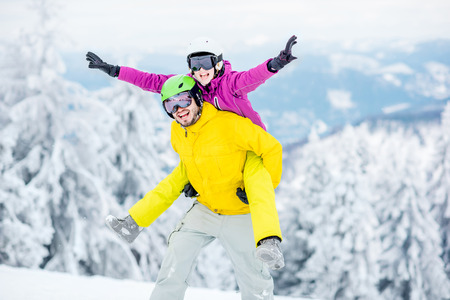 Young couple in snowboarding clothes having fun during the winter vacation on the snowy mountains Stock Photo