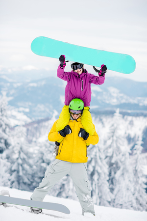 Young couple in snowboarding clothes having fun during the winter vacation on the snowy mountains 写真素材