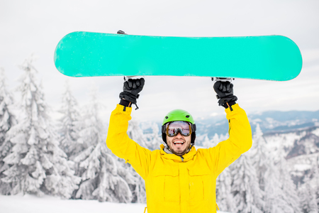 Portrait of a man dressed in winter sports clothes holding a snowboard at the mountains Stock Photo