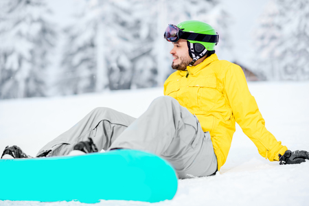 Man sitting with snowboard resting after the riding outdoors at the snowy mountains