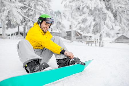 雪山の屋外でスノーボードを着た冬のスポーツ服を着た男 写真素材