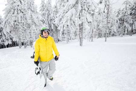눈 덮인 산에서 스노우 보드와 함께 산책하는 노란 겨울 옷을 입은 남자 스톡 콘텐츠