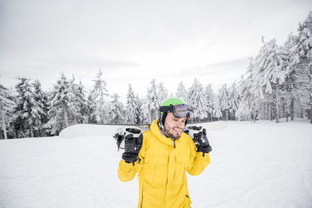 Man in yellow winter clothes walking with snowboard at the snowy mountains