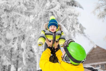 冬休み中に屋外で冬のスポット服に立って男の子と遊ぶ幸せな父親 写真素材
