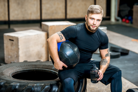 Portrait of a handsome athletic man in black sports wear sitting with ball on the tire in the crossfit gym Banque d'images
