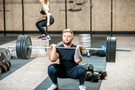 Handsome athletic man in black sports wear lifting up a heavy burbell with woman training on the background in the crossfit gym Foto de archivo