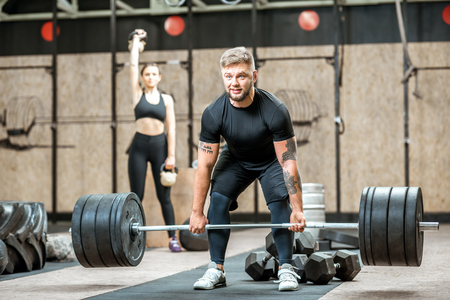 Handsome athletic man in black sports wear lifting up a heavy burbell with woman training on the background in the crossfit gym Stock Photo