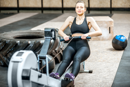 Athletic woman training on the rowing machine with big tire on the background in the gym
