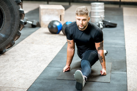 Handsome athletic man warming up stretching before the training on the floor in the gym Zdjęcie Seryjne