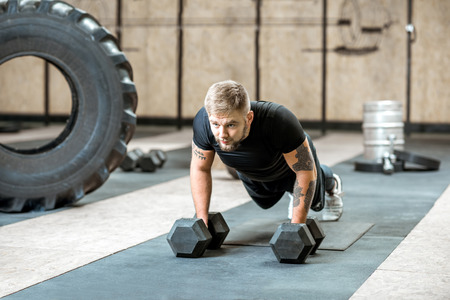 Athletic man in black sportswear with tattoos pushing ups on the dumbbells in the gym Stock Photo
