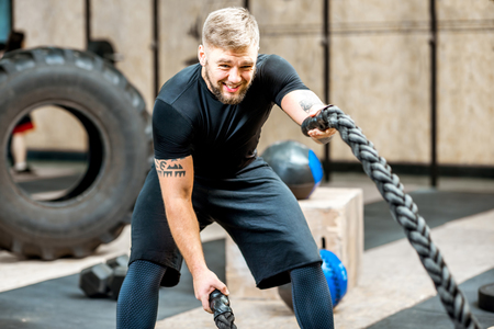 Athletic man in black sportswear swinging with a big rope training in the gym