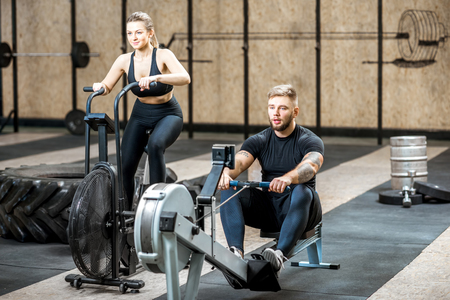 Young couple training on the exercise air bicycle and rowing machine in the gym