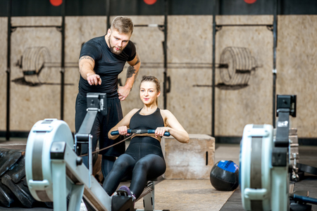 Handsome coach training woman on the exercise rowing machine in the gym Stock fotó