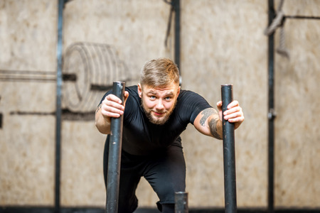 Strong man pushing sled with weights in the gym