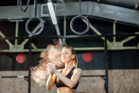 Portrait of a woman gymnast clapping hands with powder in the gym Standard-Bild