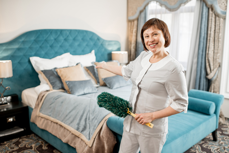 Happy senior chambermaid in uniform showing a cleaned up hotel bedroom