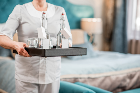 Chanmbermaid holding a tray with water in the glass bottles in the hotel bedroom. Close-up view without face