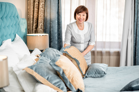 Senior chambermaid in uniform making a bed in the luxury hotel bedroom