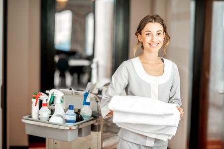 Portret młodej kobiety pokojówki trzymającej ręcznik stojącej z wózkiem pokojówki pełnym środków czyszczących na hotelowym korytarzu