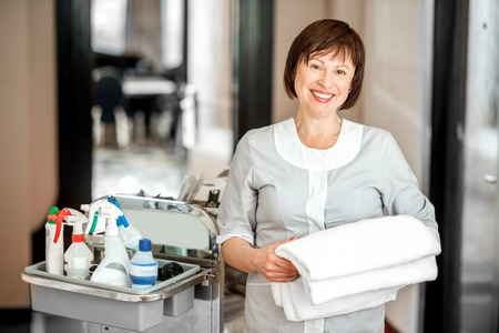 Portrait of a senior woman chambermaid standing with towel and maid cart full of cleaning stuff in the hotel corridor